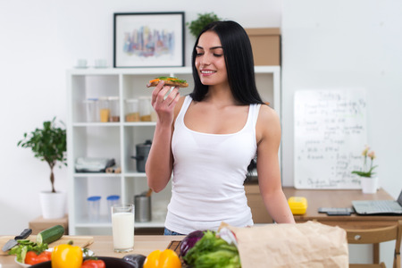 wholesome: Young woman in the kitchen having healthy breakfast, eating wholesome sandwich with vegetables and glass of milk front view portrait