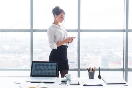 messaging: Businesswoman working in office, standing near her work table with laptop and stationary, browsing information and reading messages, using mobile device Stock Photo