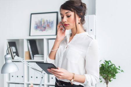 cellular: Attractive female employee speaking on the phone, having negotiations, using mobile phone and tablet in office Stock Photo