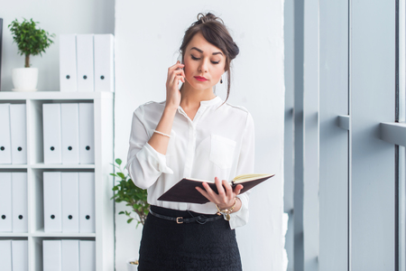 woman in office: Portrait of a businesswoman having business call, discussing details, planning her meetings using diary and cellphone Stock Photo