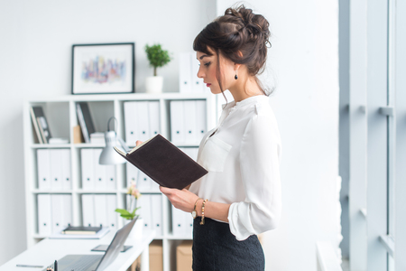 clothes organizer: Beautiful female clerk standing in office at her workplace, holding planner, reading timetable for the day, side view portrait Stock Photo