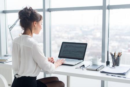 Jonge zakenvrouw werken in kantoor, te typen, met behulp van computer. Geconcentreerde vrouw zoeken naar informatie online, achteraanzicht portret