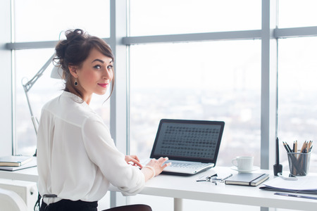 back to camera: Attractive businesswoman working at office using pc, searching and studying business ideas on a laptop screen on-line