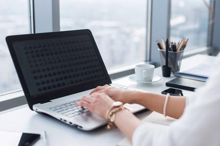 Vue latérale image des mains femme dactylographie, en utilisant pc dans un bureau de lumière. Designer de travail au lieu de travail, à la recherche de nouvelles idées