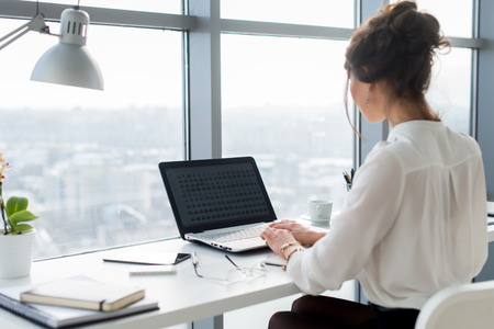 Woman wearing office suit sitting at her workplace, typing, searching new ideas for project. Female writer working with laptop on the desk