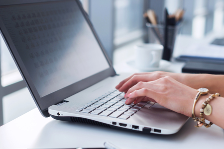 laptop keyboard: Close-up photo of female hands with accessories working on portable computer in a modern office, using keyboard Stock Photo