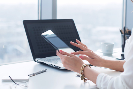 posting: Young woman holding modern tablet computer, using device at workplace during break, chatting, blogging and posting information with apps