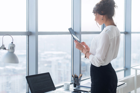 Rear view portrait of a young female office worker using apps at her tablet computer, wearing formal suit, standing near workplace, touching screen