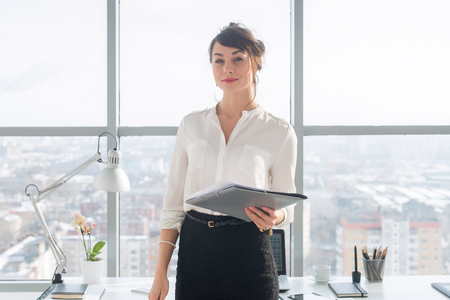 modern businesswoman: Attractive ambitious businesswoman standing in modern office, holding paper folder, looking at camera, smiling