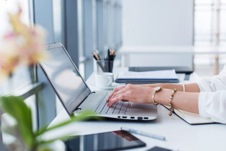 Female copywriter at her workplace, home, writing new text using laptop and Wi-Fi internet connection in the morning