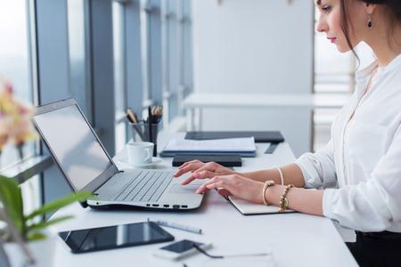 Aantrekkelijke vrouwelijke assistent werken, typen, met behulp van draagbare computer, geconcentreerd, kijken naar de monitor. Office worker lezen zakelijke e-mail