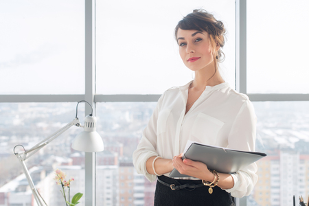 doing business: Close-up portrait of a young confident female office manager at her workplace, ready for doing business task Stock Photo
