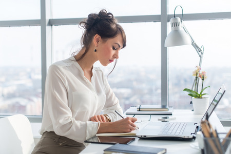 Young woman working as an office manager, planning work tasks, writing down her schedule to planner at the workplace