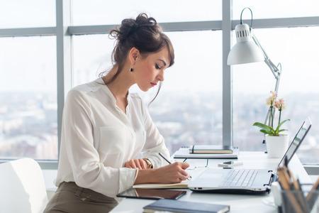 Jonge vrouw werkt als office manager, de planning van het werk taken, het opschrijven van haar schema aan planner op de werkplek