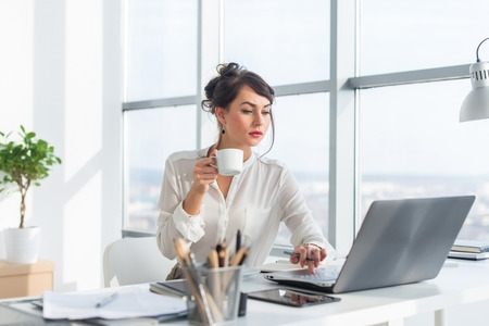 Young female business person working in office using laptop, reading and searching information attentively, drinking coffee Stock Photo