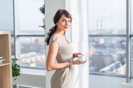 Mujer joven elegante que se coloca en un estudio de la luz amplio, beber una taza de café, sonriendo, soñando cerca de la ventana grande, que tiene descanso durante la jornada de trabajo