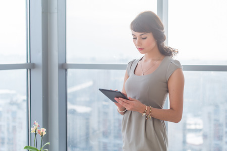 teleworker: Businesswoman standing in loft light room, typing, reading e-mail, browsing information on-line, using applications on her tablet computer