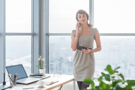 Giovane consulente femminile avendo chiamata affari in ufficio al suo posto di lavoro. Segretario parla al telefono intelligente, tenendo pda