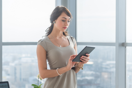 telework: Close-up portrait of a young attractive freelancer using tablet for telework, typing and reading new messages on-line Stock Photo