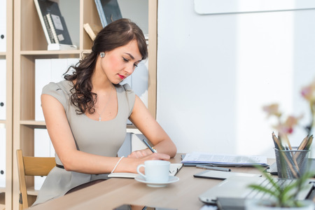 leaning: Side view portrait of a businesswoman sitting concentrated, writing, organizing her timetable in light office Stock Photo