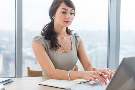 Beautiful female copywriter sitting in office, typing new article, working with text, using laptop at workplace