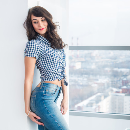 Giovane modello attraente con corpo in forma in posa in studio luce, indossa jeans e camicia a scacchi blu, in piedi lateralmente
