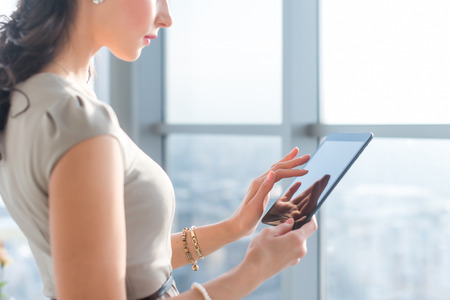 teleworker: Side view photo of young female teleworker using tablet, searching and browsing information via wi-fi connection application in office or at home Stock Photo