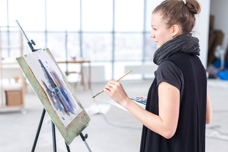 aquarelle painting art: Female painter drawing in art studio using easel. Portrait of a young woman painting with aquarelle paints on white canvas, side view portrait. Stock Photo