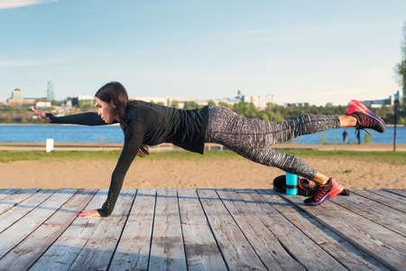 plank: Fit woman doing raised leg plank yoga pilates exercises training her abs core muscles outdoors.