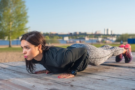 stamina: Sporty young woman doing plank exercise working on abdominal muscles and triceps exercising the river coast Stock Photo