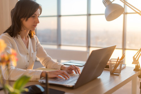 teleworker: Side view photo of a female programmer using laptop, working, typing, surfing the internet at workplace Stock Photo