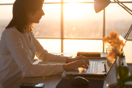 Side view photo of a female programmer using laptop, working, typing, surfing the internet at workplace Stock Photo