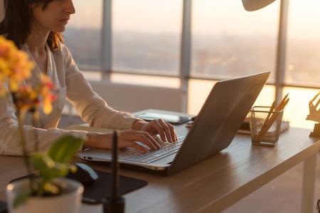 Geconcentreerde vrouwelijke werknemer te typen op de werkplek met behulp van de computer. Zijaanzicht portret van een copywriter werkt op pc thuis