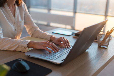 teleworker: Female teleworker texting using laptop and internet, working online. Freelancer typing at home office, workplace