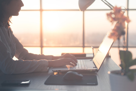 coder: Adult businesswoman working at home using computer, studying business ideas on a pc screen on-line Stock Photo
