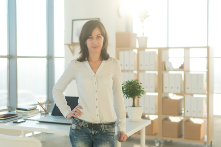 teleworker: Portrait of woman standing near workplace, looking at camera