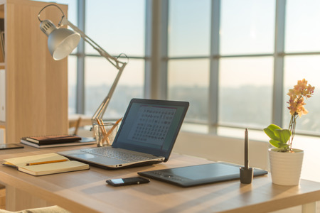 Side view picture of studio workplace with blank notebook, laptop. Designer comfortable work table, home office Archivio Fotografico