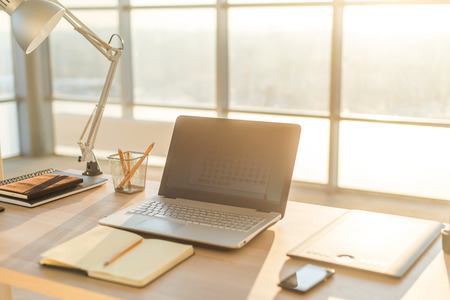 desk tidy: Side view picture of studio workplace with blank notebook, laptop. Designer comfortable work table, home office Stock Photo