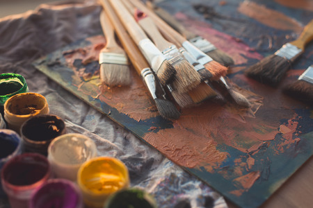 oil paint: Side view of pallet with oil paint brushstrokes under paintbrush set in an art studio Stock Photo
