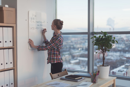 Businesswoman writing day plan on white magnet board, modern office. Side view of caucasian female employee planning schedule in morning at workplace