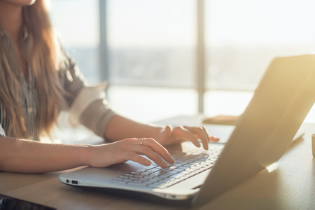 working in office: Female writer typing using laptop keyboard at her workplace in the morning. Woman writing blogs online, side view close-up picture Stock Photo