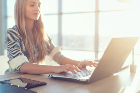 belos textos jovens copywriter fêmea de digitação e blogs em escritório claro espaçosos, seu local de trabalho, usando teclado do PC. Mulher ocupada trabalhando Imagens