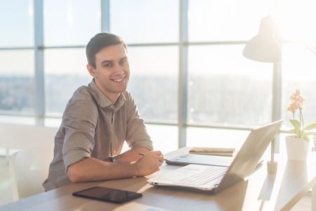 teleworker: Man using laptop on his workplace. sitting, smiling, looking at camera