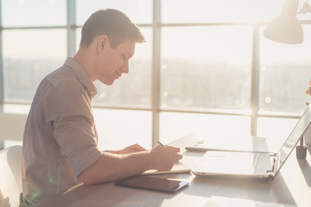 teleworker: Man freelancer writing on notebook at home or office
