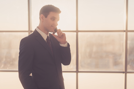 economists: Man talking on telephone while standing in modern interior with copy space