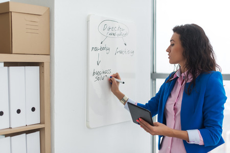 board marker: Young woman planning writing day plan on white board, holding marker in right hand.