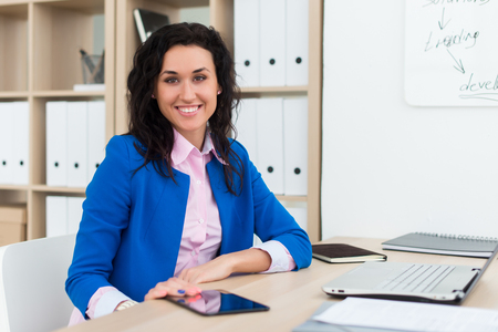 executive affable: Portrait of a woman sitting in office, smiling, looking at camera. Young confident female business worker ready for the work day Stock Photo