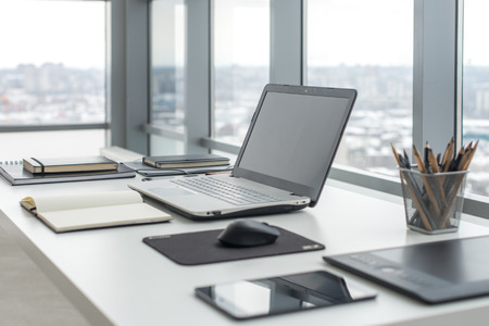 Poste de travail avec un ordinateur portable notebook confortable table de travail dans le bureau avec des fenêtres et vue sur la ville