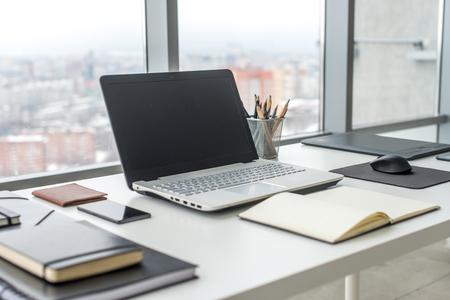 Lugar de trabajo con ordenador portátil portátil mesa de trabajo cómodo en la oficina con ventanas y vistas a la ciudad