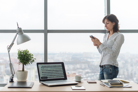 computer room: Woman with smartphone in office at her workplace. Stock Photo